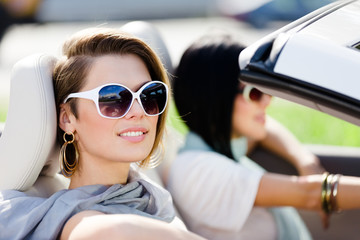 Close up of girls wearing sunglasses in the convertible car