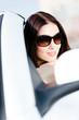 Close up of pretty female driver in the white auto