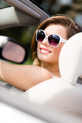 Portrait of pretty woman in sunglasses sitting in the cabriolet