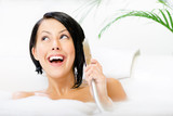 Female lying in bathtub with suds plays with shower head