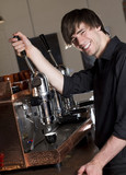 a barista smiles at the camera while brewing an espresso