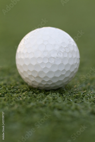 a golf ball centered on a putting green