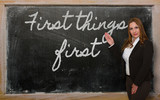 Teacher showing First things first on blackboard