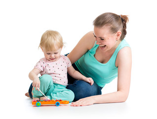 Mother and baby girl having fun with musical toy. Isolated on wh