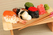delicious sushi served on wooden board on bamboo mat