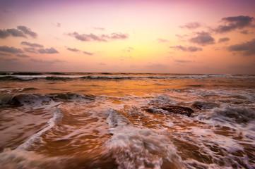 Sunset at tropical beach. Ocean sandy coast under evening sun