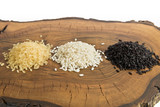 Three varieties of rice on wood cutting board