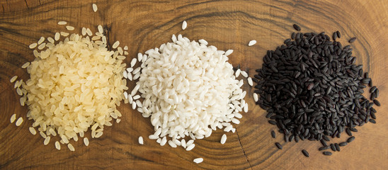 Top view of three varieties of rice on wood background