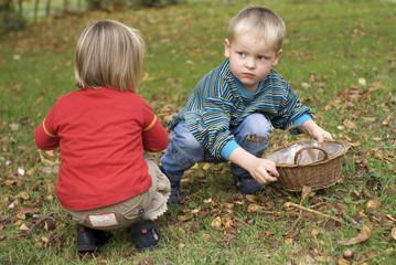 Kinder sammeln Kastanien im Herbst
