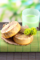 Hand made soap on grey bamboo mat, on green background