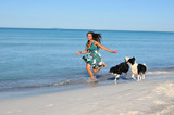 Young woman running on the beach with his dogs