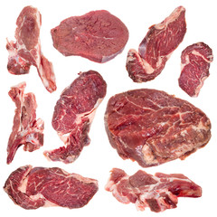 Collection of raw beef steaks and lamb chops over white