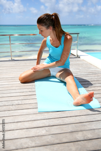 Brunette girl doing stretching exercises by the pool