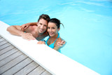 Portrait of cheerful couple in swimming-pool