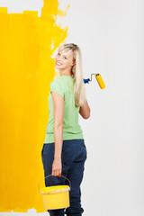 lachende frau mit farbeimer und rolle