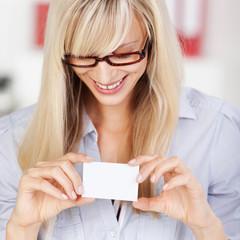 lächelnde frau schaut auf visitenkarte
