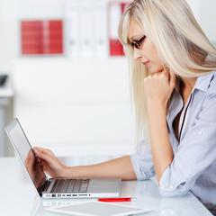 geschäftsfrau schaut konzentriert auf laptop