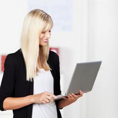 moderne geschäftsfrau schaut auf laptop