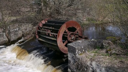 old inoperative water mill on river background