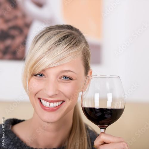 lächelnde frau stößt mit rotwein an