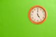 Leinwanddruck Bild - Clock showing 5 o'clock on a green wall