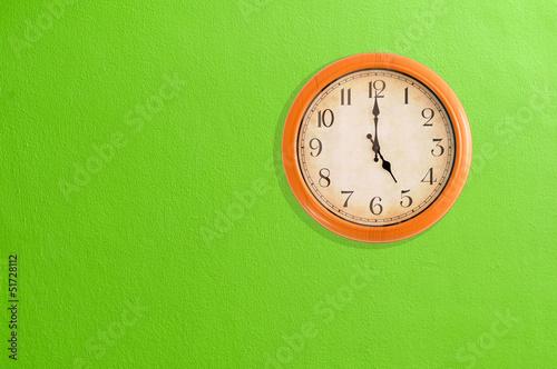 Leinwanddruck Bild Clock showing 5 o'clock on a green wall