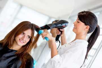 Stylist blow drying hair