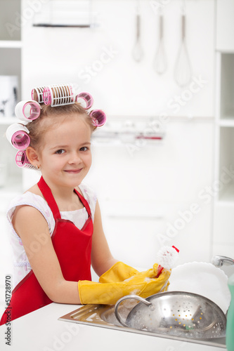 Little girl with big curls doing the dishes