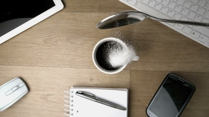 Spoon being spilled into and around a cup of coffee