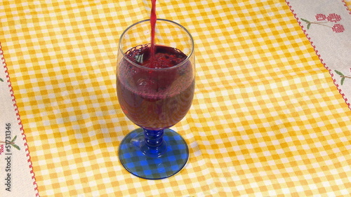 Red wine pouring in cup on table