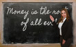 Teacher showing Money is the root of all evil on blackboard