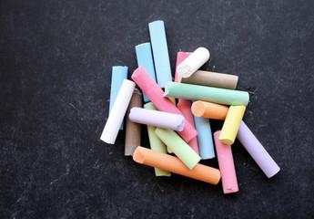 Mucchio di gessi colorati su lavagna nera