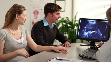 A young couple and a doctor look at an ultrasound.