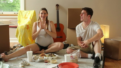 Young couple eating on the floor of their new home, dolly shot.