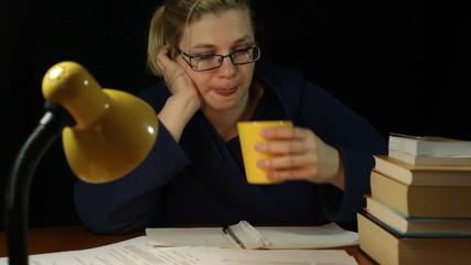 Tired woman in bathrobe working at night