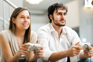 Couple playing video games on the sofa at home