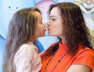 Mother and daughter kissing each other