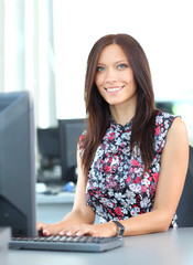 Portrait of smiling young business woman using computer