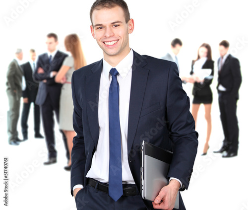 smart businessman using laptop with colleagues in the background
