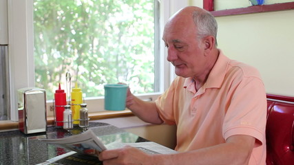 Older man drinking coffee and reading paper in a diner