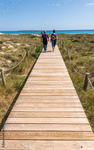 Tourists walking by beach way to Illetes beach in Formentera Bal