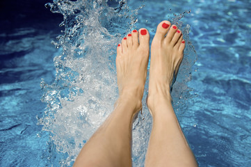 Female's feet splashing in the swimming pool water