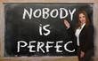 Teacher showing Nobody is perfect on blackboard