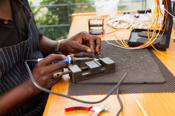 senior african electrician using soldering iron