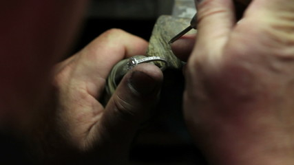 Goldsmith fixing a diamond ring in his shop