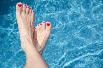 Relaxed female's feet against the swimming pool water