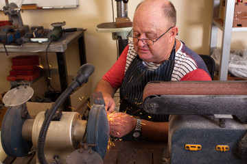 senior man using grinding machine in workshop