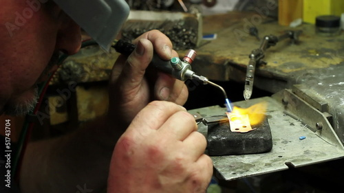 Goldsmith melting gold in his shop, dolly shot poster