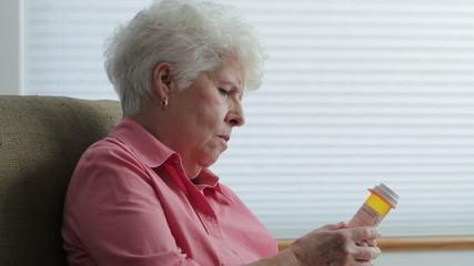Senior woman at home reading prescription bottle