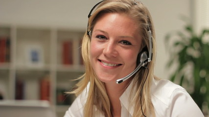 Customer service operator smiling, looking at camera, dolly shot